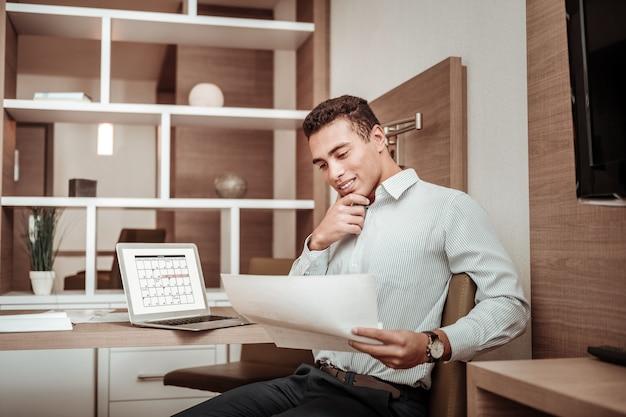 Werkschema. donkerharige zakenman die zijn werkschema in de buurt van laptop in het hotel controleert