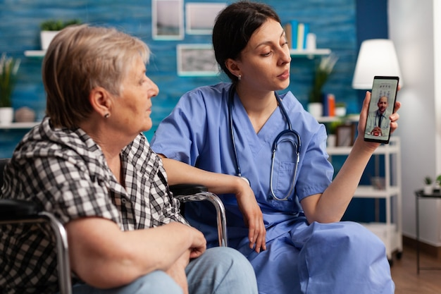 Werkster in verpleeghuis helpt gepensioneerde gehandicapte oudere vrouw met videogesprek op smartphone