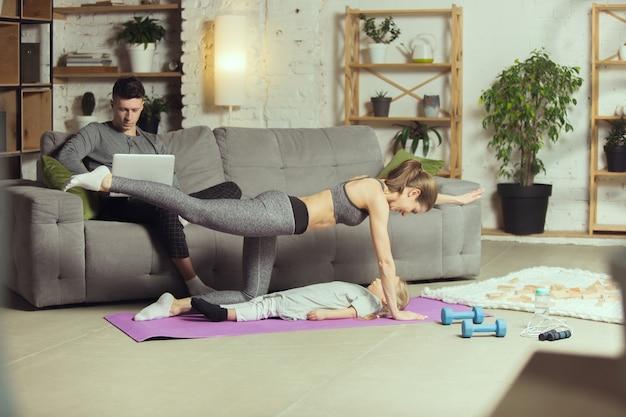 Werkt haar benen uit. jonge vrouw die fitness, aerobics, yoga thuis, sportieve levensstijl en thuisgymnastiek uitoefent