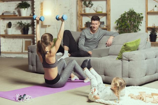 Werkt haar handen uit de mouwen. jonge vrouw die fitness, aerobics, yoga thuis, sportieve levensstijl en thuisgymnastiek uitoefent.