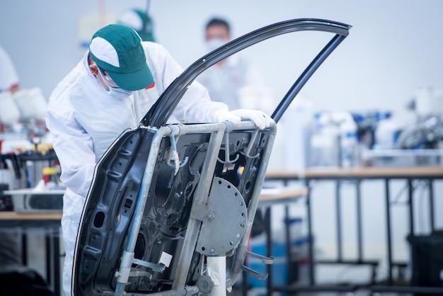 Werkt op de carrosserie door de verf voor het schilderen te primen. gebruik de kleuraanpassing voor autolak in het verfspuitlaboratorium.
