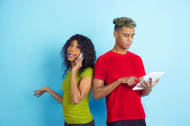 Werkt op tablet, praat via telefoon. jonge emotionele afro-amerikaanse man en vrouw in kleurrijke kleding op blauwe achtergrond. mooi paar. concept van menselijke emoties, gezichtsuitdrukkingen, relaties, advertentie.