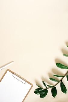 Werktafel in minimalistische stijl. computer, papier voor notities en een tak van een groene plant op een licht beige achtergrond met copyspace. plat liggen