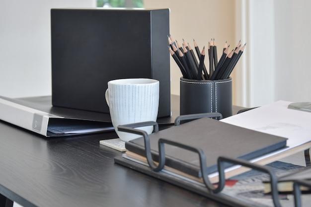 Werktafel met boek, potloden, kopje koffie en klok in een huis