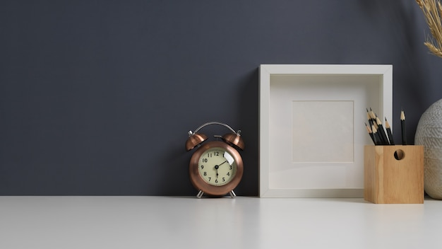 Werktafel met briefpapier, mock-up frame, wekker en kopieerruimte in thuiskantoor