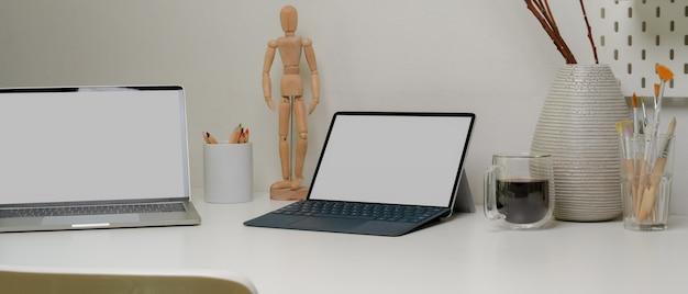 Werktafel met mock-up laptop, tablet, benodigdheden en decoratie met witte stoel