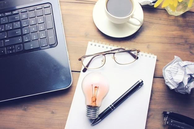 Werktafel met toetsenbord, notitieblok, telefoon, kopje koffie, bril en pen op houten tafel