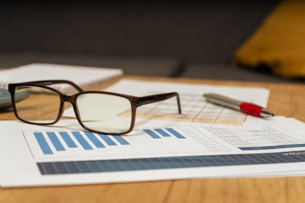 Werktafel thuis met pen, papieren, rekeningen, grafieken, glazen, computer en rekenmachine. concept thuiswerk, het controleren van rekeningen, de economie van het huis. bekijk normaal.