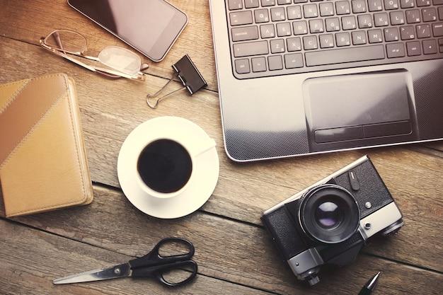 Werktafelcomputer, camera, telefoon, koffie, notitieboekje, bril, schaar op een houten tafel