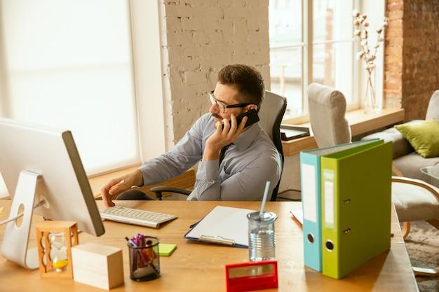 Werktijd. een jonge zakenman die zich op kantoor beweegt en een nieuwe werkplek krijgt. jonge mannelijke kantoormedewerker tijdens het beheren na promotie. ziet er blij uit