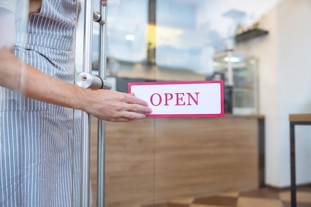 Werktijd. mannenhand in de buurt van wit bord op de voordeur met rode inscriptie open, geen gezicht