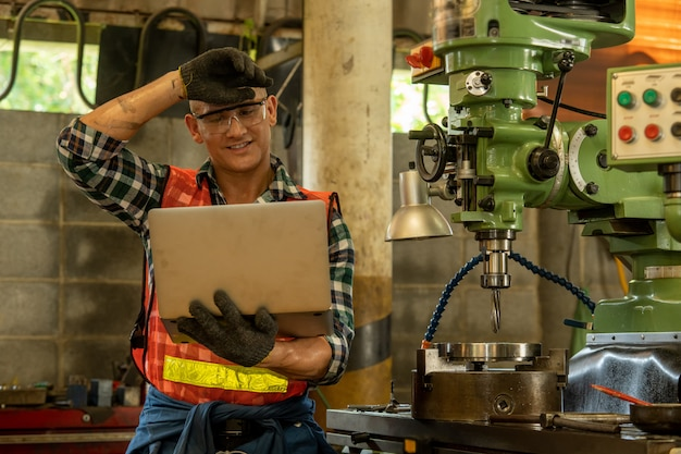 Werktuigbouwkunde die een laptop computer met het controleren van machine in fabriek met behulp van. het zware industriële werken aan metaalwerk bij machine voor de industrie van de staalstructuur