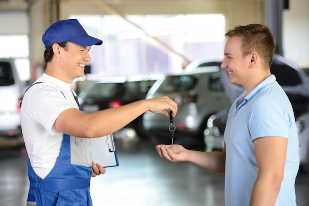 Werktuigkundige die autosleutel geeft aan een cliënt in een garage.