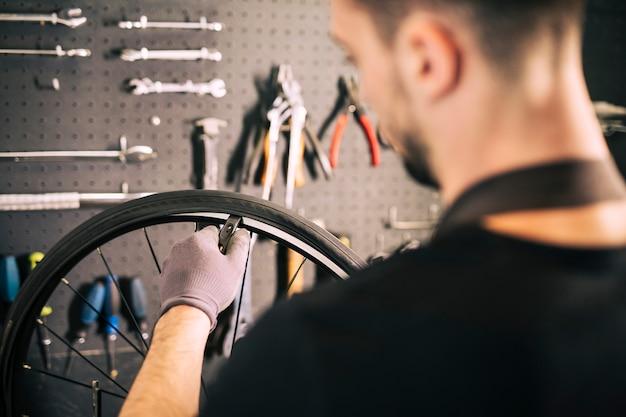 Werktuigkundige die een fiets herstelt