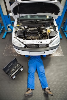 Werktuigkundige die en onder auto liggen werken