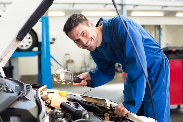 Werktuigkundige die onder kap van auto met toorts onderzoekt
