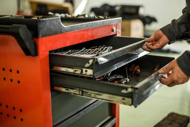Werktuigkundige die sommige hulpmiddelen zoekt voor het werk bij een autowinkel.