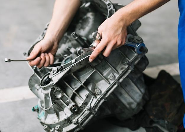 Werktuigkundige met moersleutels die motor bevestigen