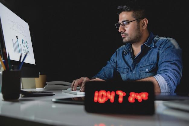Werkverslaafde man werkt overuren laat in de avond in het kantoor