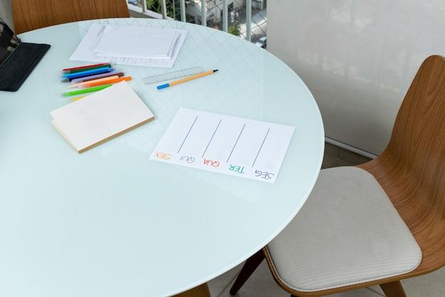 Werkvoorwerpen op een ronde tafel papieren boekpennen en tablet.