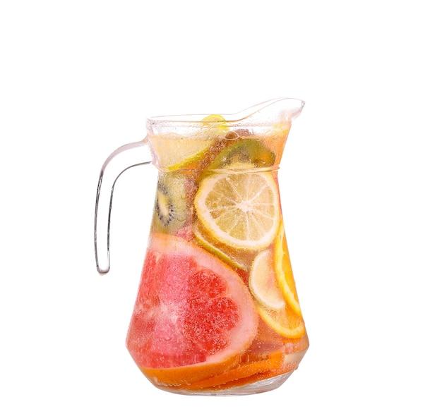 Werper met een verfrissend drankje met schijfjes citroen van sinaasappel en kiwi op witte achtergrond