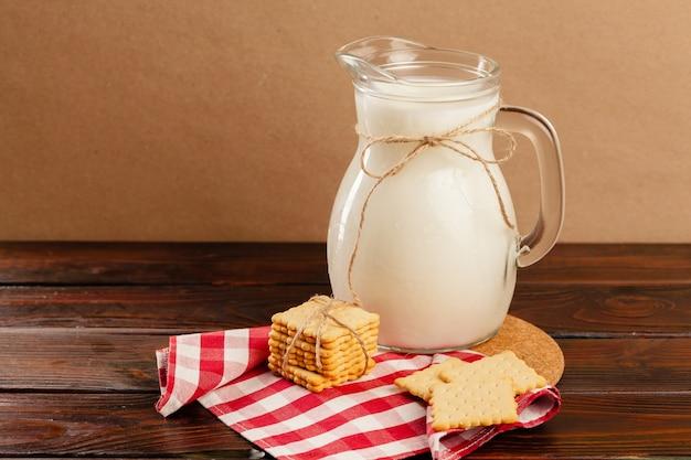 Werper van verse melk op houten tafel tegen beige close-up