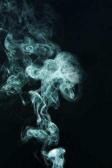 Wervelend van witte rook op zwarte achtergrond