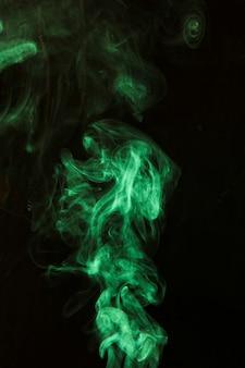 Werveling van groene rook tegen zwarte donkere achtergrond
