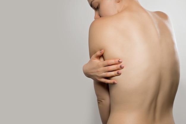 Wervelkolom osteoporose rugpijn scoliose ruggenmergproblemen op de rug van de vrouw mooie naakte vrouw die haar pijn terug aanraakt