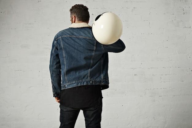 Wervelkolom weergave van biker draagt shearling denim jasje en zwart leeg henley shirt, houdt vintage beige motorhelm, geïsoleerd in het midden van witte bakstenen muur