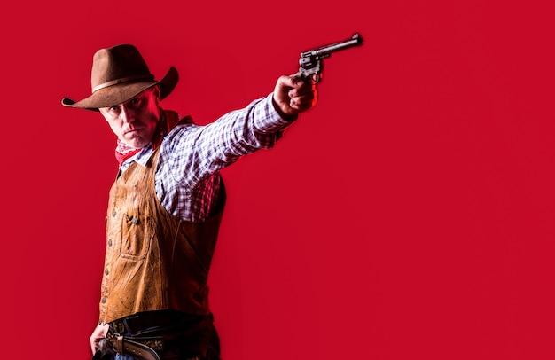 West, geweren. portret van een cowboy. owboy met wapen op rode achtergrond.
