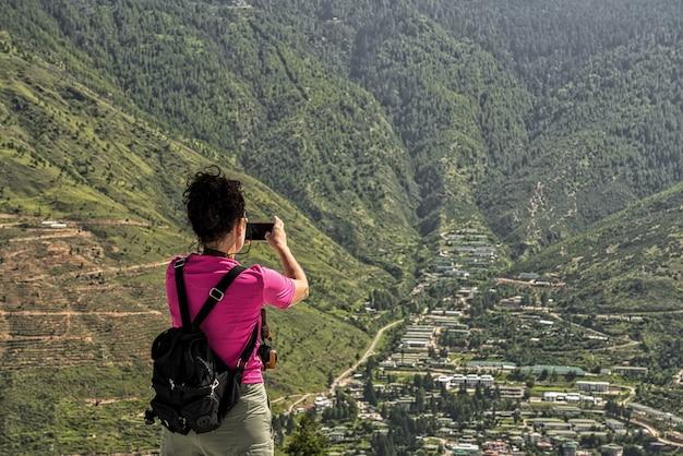Westerse toerist gril met verzameld zwart haar dat foto's neemt naar een groene vallei met bergen op de achtergrond in buthan. himalaya. rose t-shirt en kleine zwarte rugzak