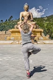 Westerse toerist van achteren met blond golvend haar in verticale yogapositie op de explanda voor het boeddha dordenma-standbeeld in buthan. de langste boeddha ter wereld. gouden boeddha. grijze kleding