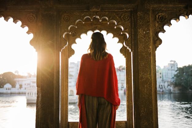 Westerse vrouw die zich op een culturele architectuur in udaipur, india