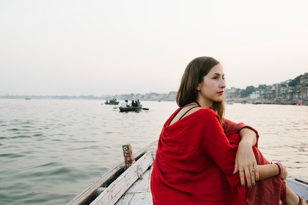 Westerse vrouw op een boot die de rivier de ganges verkent
