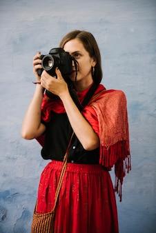 Westerse vrouwelijke fotograaf die een stad van udaipur, india onderzoekt