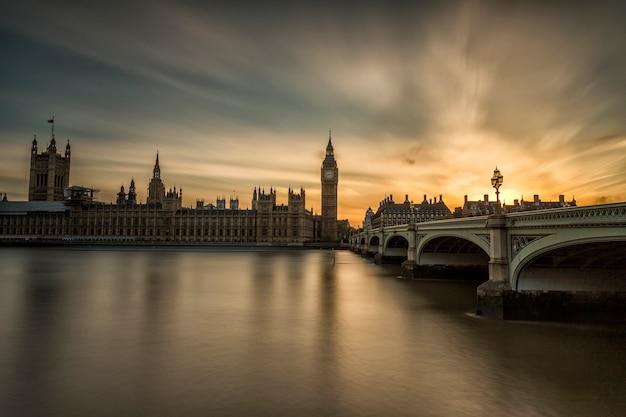 Westminster abbey en big ben over de theems in londen met reflectie op de rivier