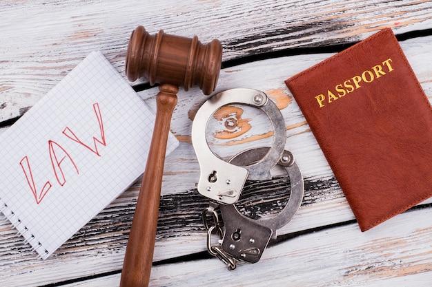 Wet en bureaucratie concept. rechter hamer met handboeien en paspoort op witte houten tafel.