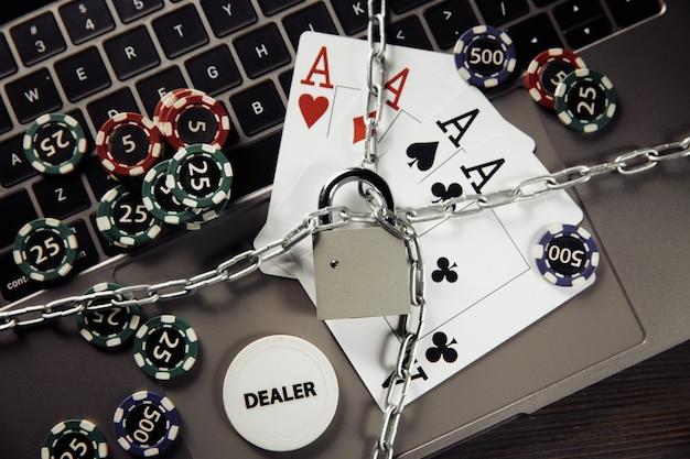 Wet en regels voor online gokconcept, hangslot en playng-kaarten op laptop toetsenbordclose-up.