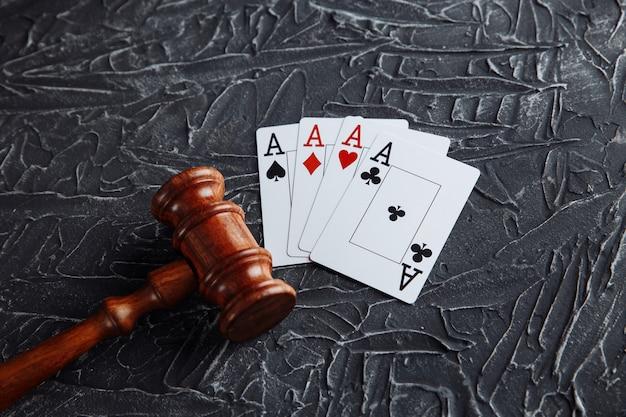 Wet en regels voor online gokken concept, rechter hamer met playng kaarten op grijze achtergrond.