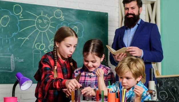 Wetenschap en onderwijs. scheikunde lab. terug naar school. gelukkige kinderen en leraar. kinderen die wetenschappelijke experimenten doen. experimenten doen met vloeistoffen in het scheikundelab. verbetering van de moderne geneeskunde.