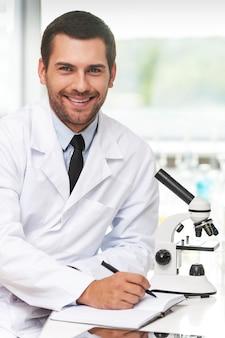 Wetenschap is mijn leven. glimlachende jonge wetenschapper in wit uniform die in zijn notitieblok schrijft en naar de camera kijkt terwijl hij op zijn werkplek zit