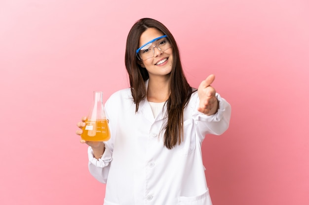 Wetenschappelijk meisje over geïsoleerde roze achtergrond handen schudden voor het sluiten van een goede deal