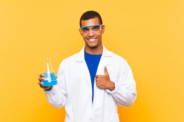 Wetenschappelijke mens die een laboratoriumfles over muur met omhoog duimen houdt omdat iets goeds is gebeurd