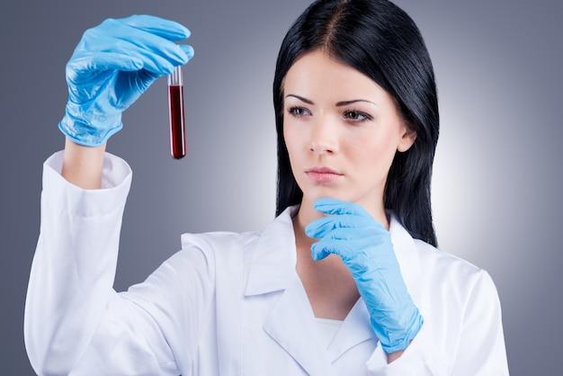 Wetenschappelijke onderzoeken. vrouwelijke arts in wit uniform die een kolf met bloed vasthoudt terwijl hij tegen een grijze achtergrond staat