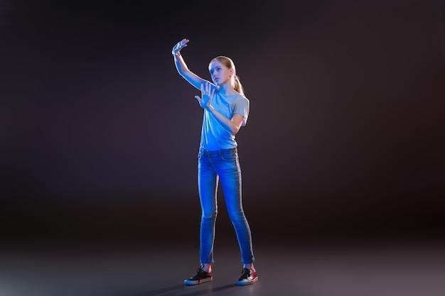 Wetenschappelijke ontwikkeling. aantrekkelijke blonde vrouw met behulp van moderne technologie terwijl staande tegen een zwarte achtergrond