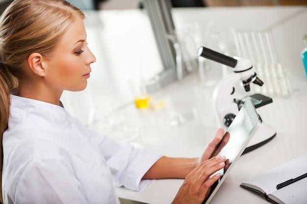 Wetenschapper aan het werk. bovenaanzicht van jonge vrouwelijke wetenschapper die aan digitale tablet werkt terwijl ze op haar werkplek in het laboratorium zit