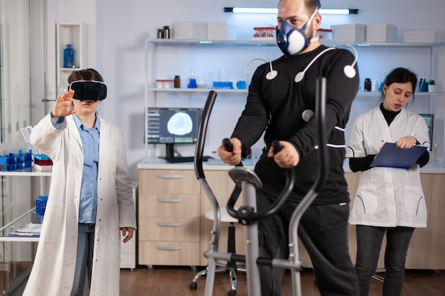 Wetenschapper-arts in het sportwetenschappelijk laboratorium die een virtual reality-bril draagt terwijl de atleet rent, met elektroden op het lichaam bevestigd die het fysieke uithoudingsvermogen controleren terwijl de ekg-scan op het computerscherm wordt uitgevoerd