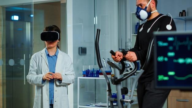 Wetenschapper-arts in het sportwetenschappelijk laboratorium met een virtual reality-bril terwijl de atleet loopt met elektroden die zijn bevestigd op het lichaam en het fysieke uithoudingsvermogen bewaakt terwijl de ekg-scan op het computerscherm wordt uitgevoerd.