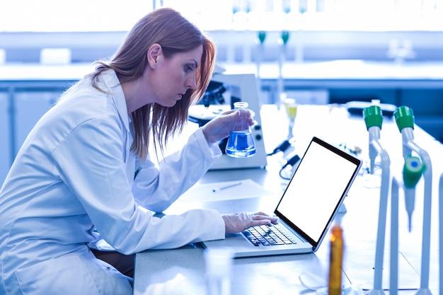 Wetenschapper die beker van chemisch product bekijkt